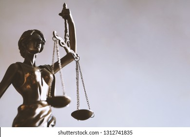 lady justice or justitia - blindfolded figurine holding balance scales - law jurisprudence and impartiality symbol - background with copy space
