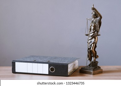 lady justice or justitia statue and file folder on desk - law and legal concept - background with copy space