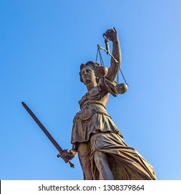 Lady Justice standing at the fountain under blue sky in Frankfurt as a symbol of justice