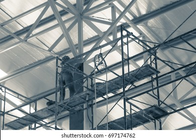 lady labor worker is working at high level risk on metal scaffolding, she working for ceiling structure roofing