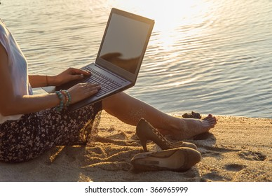 Lady with a laptop on the beach on the sunset