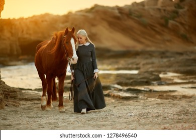 lady leads a horse at sunset along the seashore in a historic costume of the 19th century.