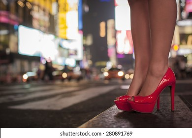 Lady legs with red high heel shoes at Time Square in New York City during night time.