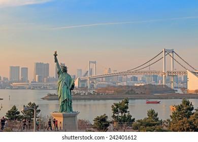 Lady liberty juxtaposed against Rainbow Bridge in Tokyo