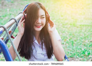 Lady listening music from smart phone with headphones outdoor at a park.