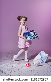 Lady little girl in beautiful pink dress with gift present box. Fashion child.Holidays, christmas, new year, x-mas concept. Full length portrait smiling kid posing in studio, pink background.