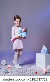 Lady little girl in beautiful pink dress with gift present box. Fashion child model.Holidays, christmas, new year, x-mas concept. Full length kid posing in studio, isolated pink background.