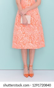Lady in long floral pattern sundress with white purse and orange high hell shoes posing gray background