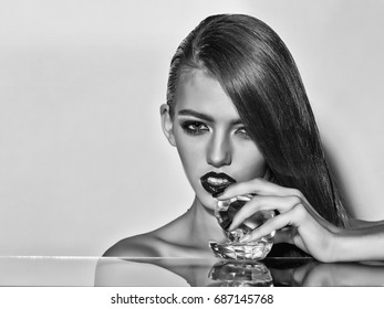 lady with long hair has bright lips with glassy decorative shell with pearl, black and white