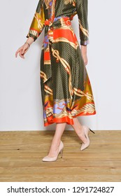 Lady in long sundress with with a belt, fashion pattern. and black shoes posing wooden background