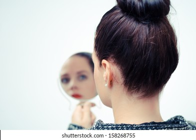lady looking in a hand mirror with white background