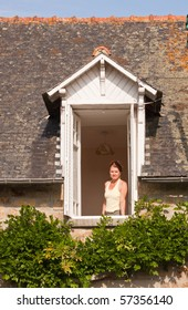 A lady looking out of the open window of an old country house