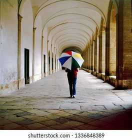Lady with multi colored umbrella walking in the galleries of the central square of Marciac, France. This village is well known because of its yearly Jazz Festival