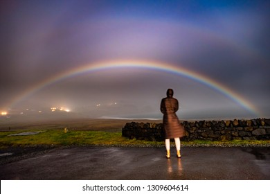 Lady observing very rare moonbow during the night above Staffin bay - Isle of Skye, Scotland.
