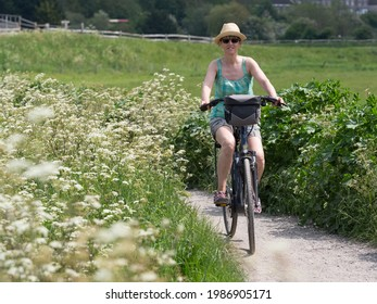 A lady on her electric bike cycles on a cycle route path between white wild flowers.She has handlebar bag and wears a straw hat and sunglasses.