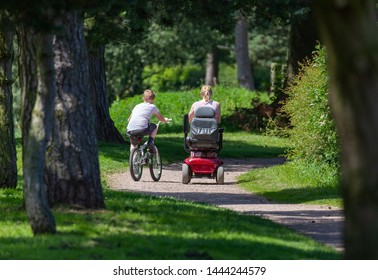 A lady on a mobility vehicle with a teenage boy riding a bicycle on a woodland path together.