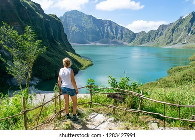 Lady on ridge overlooking crater lake of Mt. Pinatubo - Luzon, Philippines