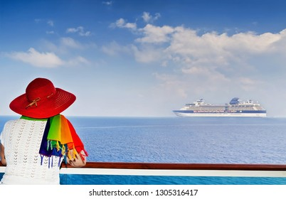 Lady on the ship looking at cruise ship sailing from port