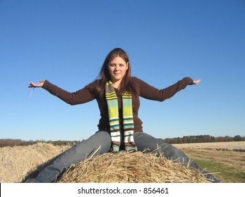 Lady with outstretched arms on hay roll.