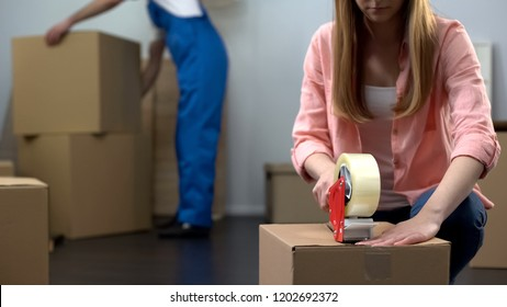 Lady packing things in box, moving company worker carrying baggage, services
