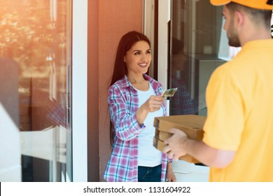 Lady paying for pizza delivery. Sweet beautiful woman handing cash money to pizza delivery guy who is dressed in yellow uniform.