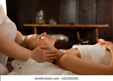 Lady peacefully lying. Young beautiful woman with closed eyes being in calm atmosphere while master massaging her neck