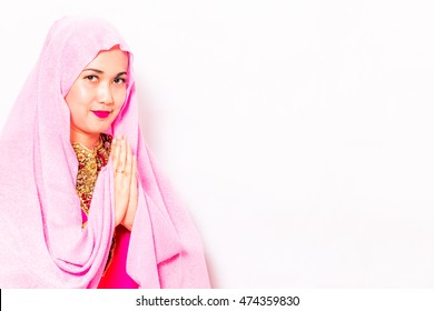Lady with pink veil crosses her hand to congrats or salute