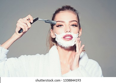 Lady play with sharp blade of straight razor. Girl on dreamy face wears bathrobe, grey background. Woman with face covered with foam holds straight razor in hand. Barber and shaving concept
