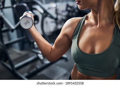 Lady practicing bodybuilding among the gym machines while raising one metal dumbbell with a muscular hand