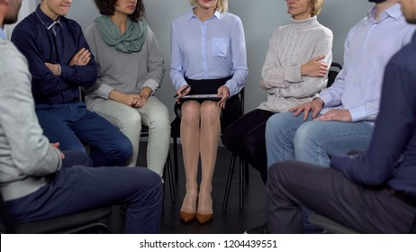 Lady psychotherapist meeting group of her patients sitting in circle and talking