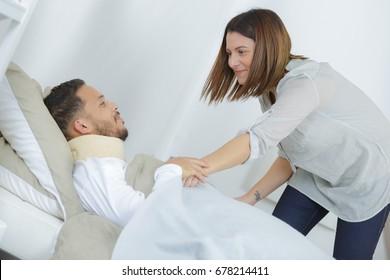 lady pulling blanket up over injured man