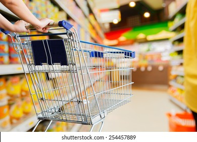 Lady pushing empty shopping cart in the supermarket