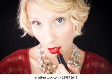 Lady putting lipstick (like in front of a mirror) Beautiful lady with an old fashioned style shot in studio with a black background.