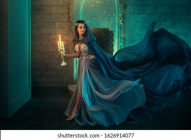 lady Queen woman medieval royal dress run escapes from Gothic night castle. Blue silk dress, cloak train plume waving motion. Holds in hands old candlestick burning candles. Background old retro room