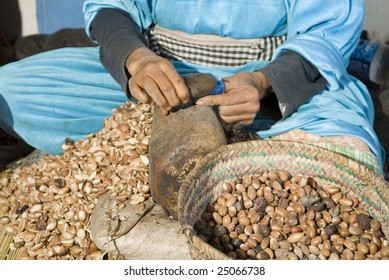 Lady racking argan nuts by hand with a stone