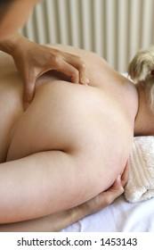 A lady receiving a shoulder massage as part of a holistic massage treatment