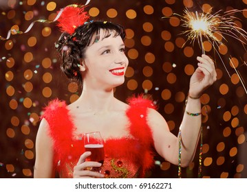 Lady in red dress at the carnival with champagne flute and Bengal light at the flames background