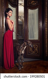 lady in red dress with greyhound