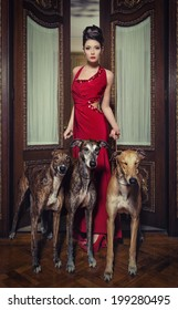 lady in red dress with greyhounds