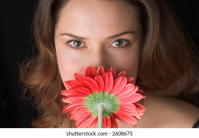 Lady with red gerber smelling the flower. Straight close up portrait