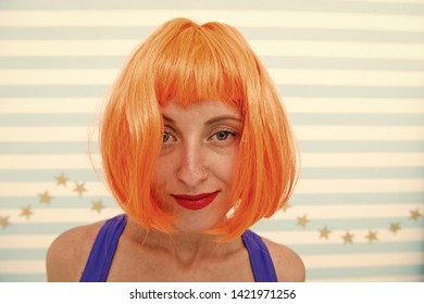 Lady red ginger wig and make up close up. Coloring and treatment professional salon service. Wig bright artificial hair looks unnatural. Hair revival procedure advice. Cosmetics for care and revival.