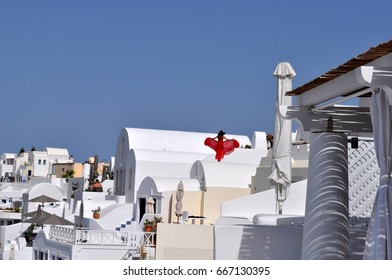Lady in red on rooftop in Oia on the island of Santorini in Greece