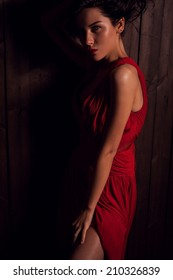 Lady in red pose on wooden background. Close-up photo.
