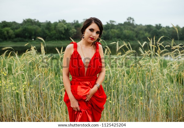 Lady in red with smoky eyes is posing outdoors