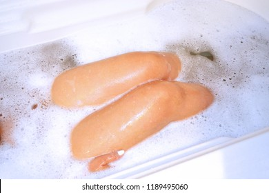 A lady relaxing in a hot bubble bath showing some body parts