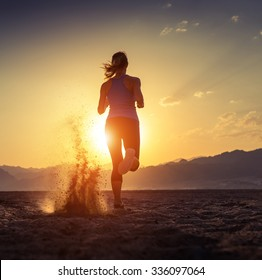 Lady running in the desert at sunset