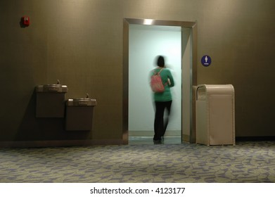 A lady rushing to the washroom (toilet)
