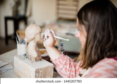 Lady sculptor working in her studio, ceramis artist's hands