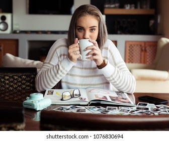 Lady with a serious look  looking straight into the lens while drinking her coffee.