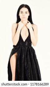 Lady, sexy girl in dress. Attractive girl wears expensive fashionable evening dress with erotic slit. Woman in elegant black evening dress with decollete, white background. Sexy decollete concept.